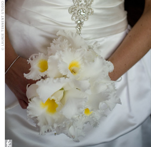 The bride carried a hand-tied bouquet of white cattleya orchids.