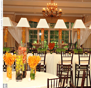 Cylinder vases filled with orchids topped round tables covered in cream linens and surrounded by mahogany chiavari chairs. Other vases overflowing with cymbidium orchids and topped with white lamp shades decorated the long high-top table.