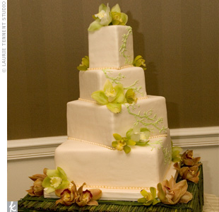 Hand-painted vines and fresh cymbidium orchids covered the four-tiered cake.