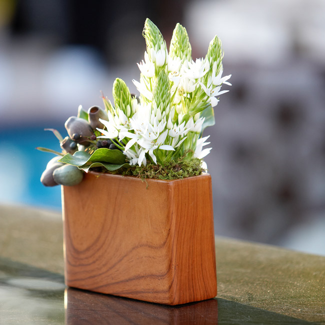 The ranch-chic theme continued with rectangular carved wood boxes filled with rustic pods, blooms, and foliage.