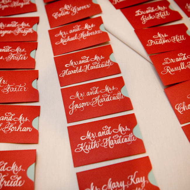 "The talented bride also created the escort cards, which were aqua cards set in small red envelopes with the guests' names written in white. ""I was completing these minutes before the ceremony!"" admits Hayley."