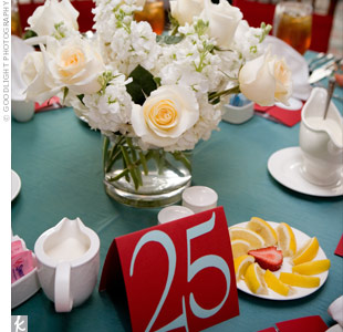 "The bride's design studio created the couple's bright, cheerful table numbers. Centerpieces of all-white blooms varied in height throughout the room, and some tables held metal ""trees"" of votive candles."
