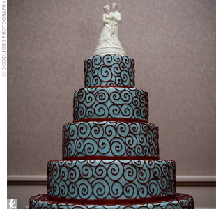 Hayley and Jason's five-tiered cake was frosted in aqua-hued buttercream accented with a pattern of red fondant. A family heirloom cake topper of a Belleek Irish porcelain bride and groom that belonged to the bride's maternal grandmother topped off the confection.