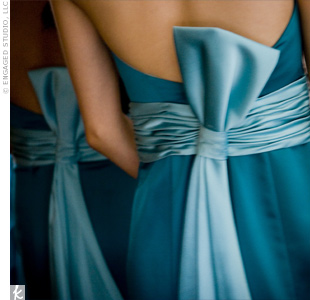 "Mai-An chose the dark teal hue of her bridesmaid dresses because it fit the summer season but was still formal. Her seven bridesmaids wore strapless, satin, A-line dresses with a contrasting sash and half-bow in back. Though the dresses came with brooches, the bride chose to take them off to give them a ""clean and simple look."""