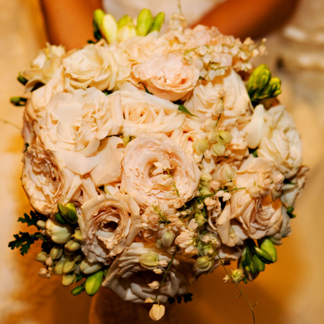 "Ashley carried a loosely packed bouquet of roses and coral vine in ivory, with a few hints of pink and green. A linen handkerchief belonging to her great aunt was wrapped with the stems for the bride's ""something old."""