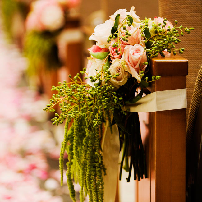 Clusters of hanging amarynthus tied with light pink ribbon hung from the pews along the aisle.