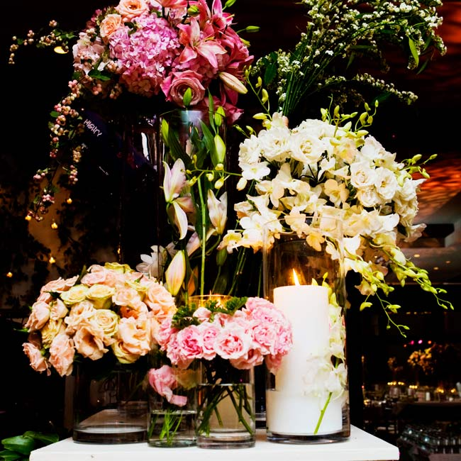 On either side of the stage for the band, a pair of tall ivory pedestals stood topped with a collection of vases filled with flowers, vines, and candles. Behind the band the wall was draped with Elaeagnus and wild rose vines.