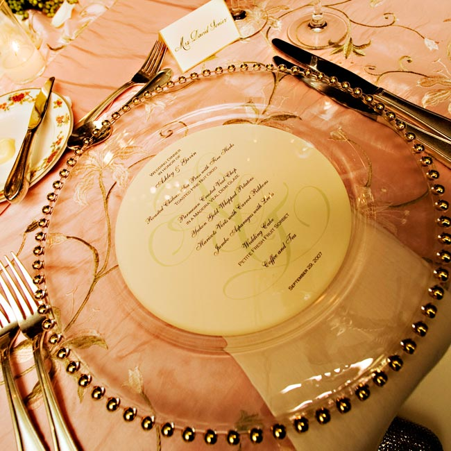 The circular menu cards could be seen perfectly underneath round, glass chargers with gold-beaded edges.
