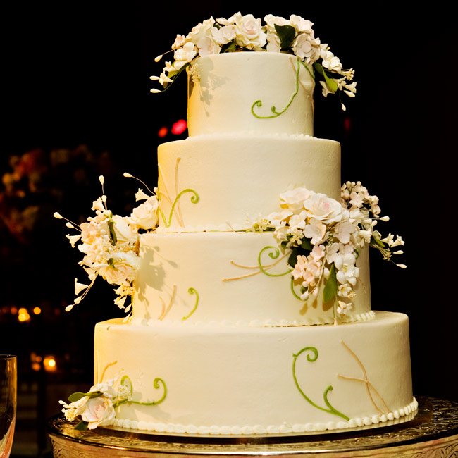 Ashley and Gavin's guests enjoyed a four-tiered cake decorated with pink gumpaste flowers and green and brown leaves and branches. Pale pink rose petals and Majolica spray roses adorned the cake table.