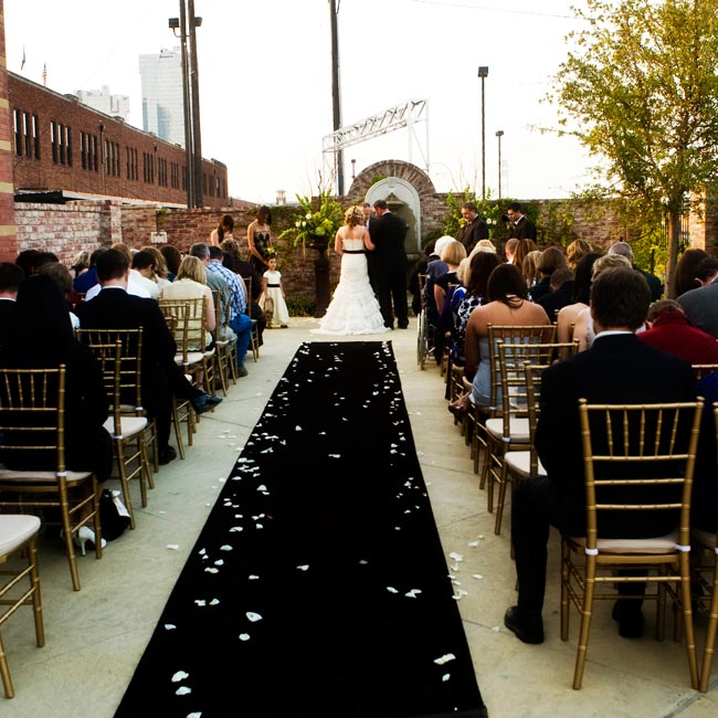 Kristle and Todd stood before a fountain marked off on both sides with large brown urns filled with orchids and bells of Ireland. A brown velvet runner with orchid blossoms and flower petals scattered along the sides led the way to the altar.