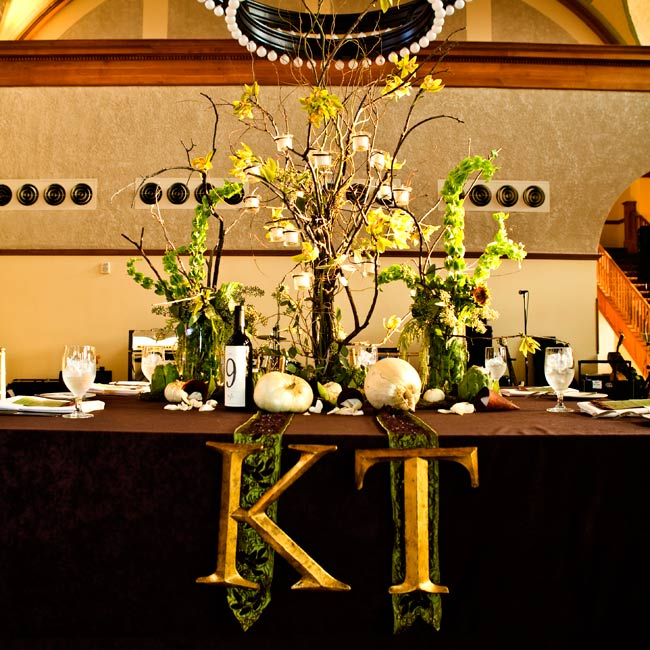 At the reception, the couple's initials were hung on the head table from green and brown ribbons.