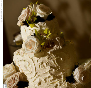 Kristle and Todd's bride's cake was a three-tier almond cake covered in ivory amaretto frosting. It was adorned with champagne roses, ferns, and green orchids.