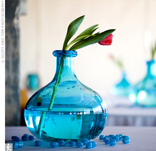 The red tulips in the centerpieces not only held sentimental value, they achieved that sleek and modern look Leigh wanted, when arranged in turquoise glass vases.