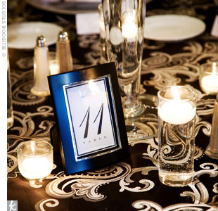 Framed table numbers sat next to cylinders filled with floating white candles.