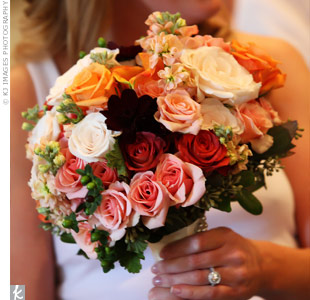 Myndi held a bouquet of roses, hydrangea, coxcomb, calla lilies, monkey tails, and berries in fall hues.