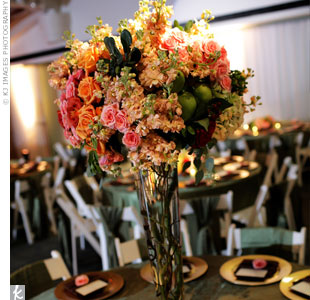 Roses, hydrangeas, and berries filled \glass trumpet vases on guest tables. Amber-colored votives were clustered around the centerpiece.