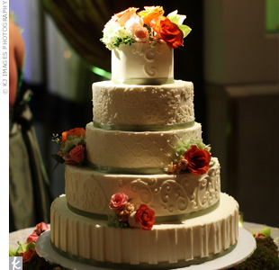 The five-tiered, vanilla cake was decorated with a white brocade pattern and the couple&#39;s monogram. Fresh flowers and cypress green ribbon added color.