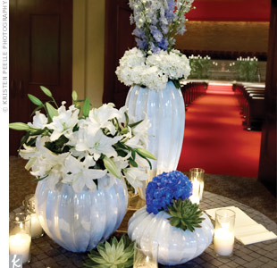 Modern arrangements of glossy white vases filled with lilies, hydrangeas, succulents, and orchids decorated the guest book table.
