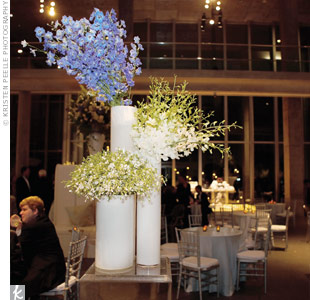 Arrangements of hydrangeas, stephanotis, and Mexican gardenias filled white column vases.