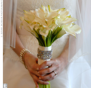 Julie opted for a simple, elegant bouquet of all white, long-stemmed calla lilies. They were wrapped in all white ribbon and got an extra bit of bling thanks to a band of diamonds.