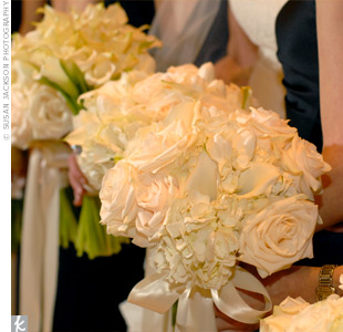 Each of the bride's attendants held a full, lush all-white bouquet that included cream-colored roses and hydrangeas. The stems were wrapped in white satin ribbon that trailed nearly to the floor.