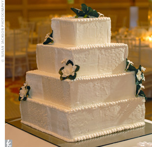 Julie and David cut into a four-tiered, square cake iced in buttercream and adorned with fresh gardenias and stephanotis.