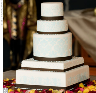The five tiers of the cake varied in size and shape. Each tier was wrapped in brown ribbon and covered in a pale damask pattern. The confection was topped off with edible pearls.