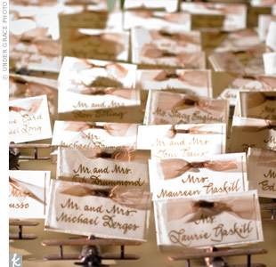 Each guest's name was calligraphed on velum, which was attached to handmade paper with brown ribbon. The cards sat atop little bronze airplanes -- mementos of the reception site, and also pencil sharpeners!