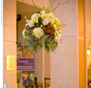 Lush arrangements were set high on slim glass pillars, so guests could easily talk to one another without the centerpieces blocking their view.