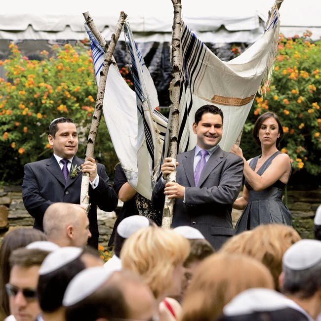 Lauren and Josh's huppah was made from four talit (Jewish prayer shawls) -- belonging to the groom, his father and grandfather, and Lauren's father. They were tied to four birch poles, each held by the couple's close friends, who carried the huppah down the aisle together.