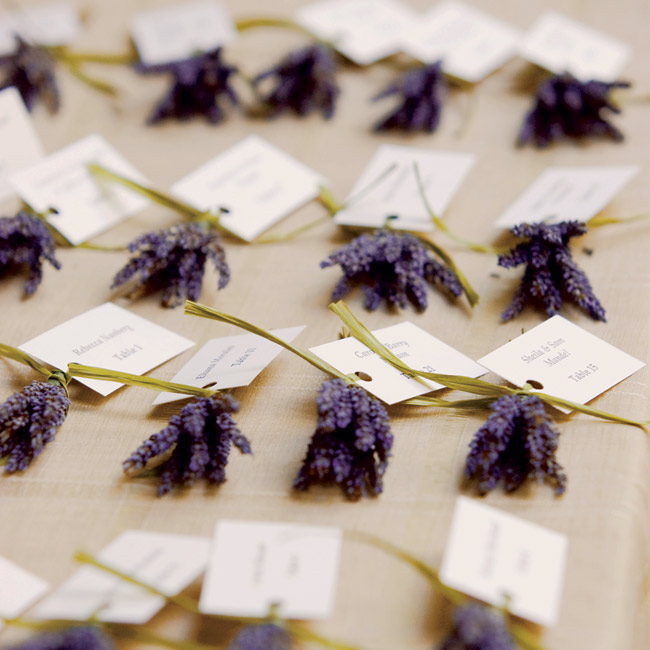 The mother of the groom created the escort cards, which were accented with lavender and raffia. Guests picked them up from a table adorned with vases of lavender, pomegranates, sunflowers, topiaries, and lanterns.