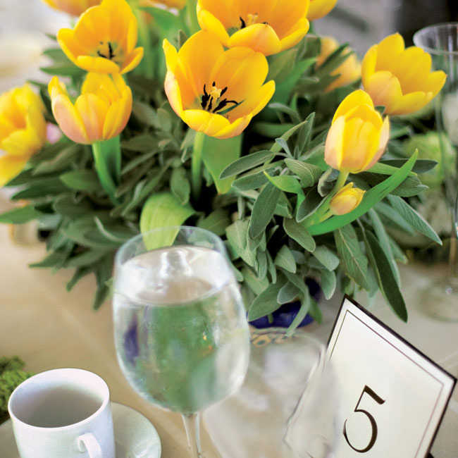 An eclectic mix of centerpieces, including bright yellow potted tulips, topped the tables.