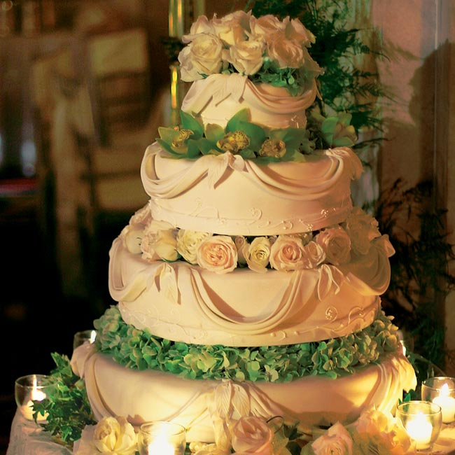 Although Alexis and Alberto didn't serve wedding cake, they decided to keep with tradition and still displayed one -- just the top tier, which the couple cut, was real. The four tiers were separated with fresh flowers and draped in fondant icing.