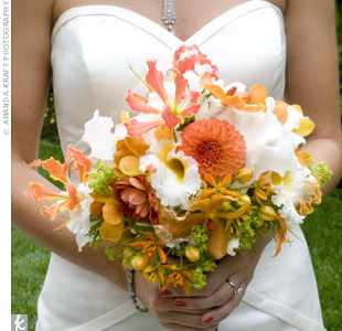 Kate's exotic bouquet combined different shapes and textures with blooms such as orchids, scabiosa, and spider mums in an explosion of orange and white. It was hand-tied with a black and white ribbon.