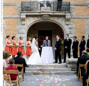 A scattering of white and orange rose petals decorated the aisle and two large urns overflowing with wild, tropical blooms flanked each side of the altar. The couple chose to personalize their ceremony by writing their own vows.