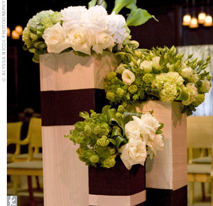 The ceremony was decorated with silk-wrapped boxes filled with white and green lisianthuses, anemones, and roses.