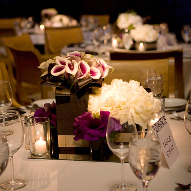 Three boxes of varying sizes wrapped in silk and filled with white flowers accompanied three vases filled with purple flowers as well as three small votives to create a variety of heights and shapes on the tables.