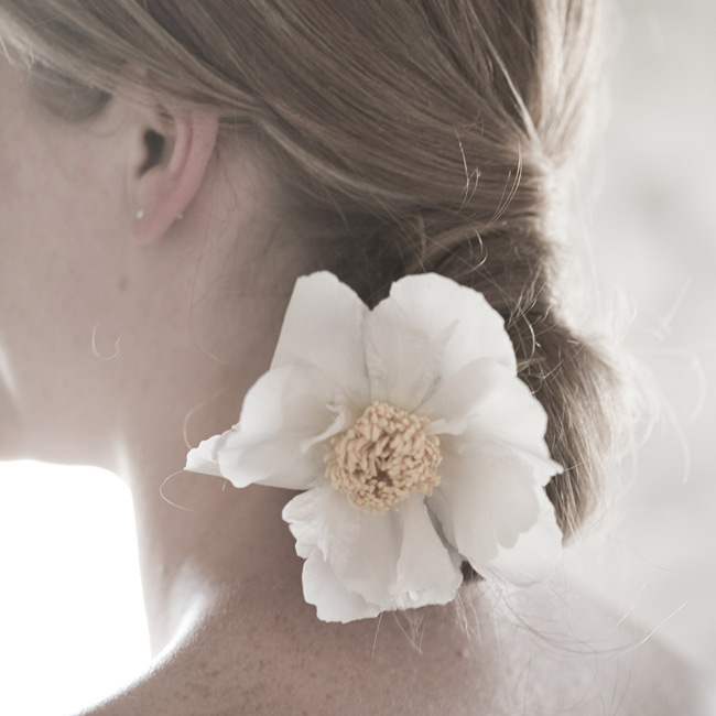 Courtney's hair was worn to the side in a chignon accented with a peony.