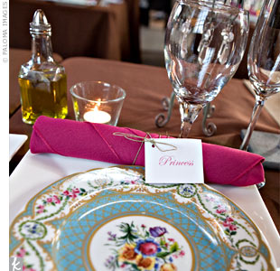 Long banquet tables were draped with chocolate brown linens and topped with white square bistro plates. The raspberry-colored napkins were rolled up with flatware and tied with twine.