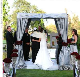 The couple wed under a huppah designed by the bride. Made to look like a VIP cabana, it was draped in silver duponi silk that was tied back with an arrangement of red roses.