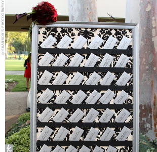 The escort cards were placed on three large easels covered in black and cream damask fabric and topped with floral arrangements of black magic roses with plum calla lilies. Each card was placed in a silver envelope addressed with calligraphy.