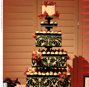 In lieu of a cake, the couple wanted a tower of mini cupcakes in an assortment of delicious flavors like key lime, Meyer lemon-raspberry, vanilla bean and chocolate ganache. Each tier was covered in black and cream damask fabric and trimmed with orchids and crystal brooches. The top tier held a small square cake for cutting.