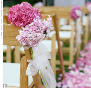 The aisle was scattered with hundreds of pink rose petals and lined with wooden chairs adorned with pink hydrangeas and white ribbon.