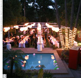 Mary's parents' backyard was transformed into a chic reception site with long, rectangular tables and hanging pink paper lanterns while pink and green balloons floated in the illuminated pool.