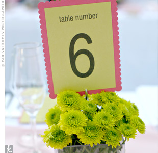 Pink scalloped edge table cards layered with light green paper popped out of vases filled with Kermit mums.