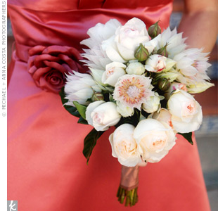 A perfect complement to the bright coral dresses, the bridesmaids carried light pink Blushing Bride protea and soft pink garden roses.