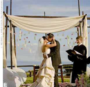 Overlooking the sea, the couple wed underneath a canopy of bamboo draped in sheer ivory fabric and white and pink orchids.