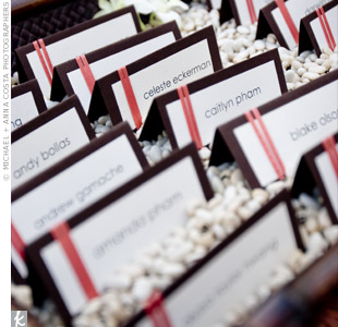 For a modern touch, the couple created escort cards from chocolate and white paper and added strands of satin coral ribbon. The cards were placed in a wooden tray of neutral-colored lima beans and decorated with white orchids.