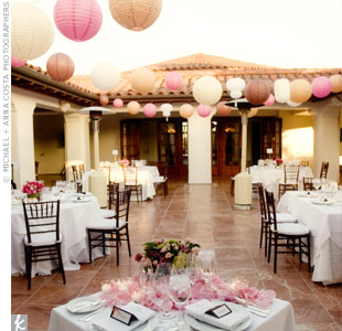 White, pink and blush paper lanterns dangled over tables covered in white linens and accented with pink floral centerpieces.