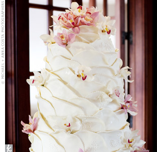 Inspired by the layers of the bride's skirt, the three-tiered cake was covered in white fondant made to look like the petals of a flower.